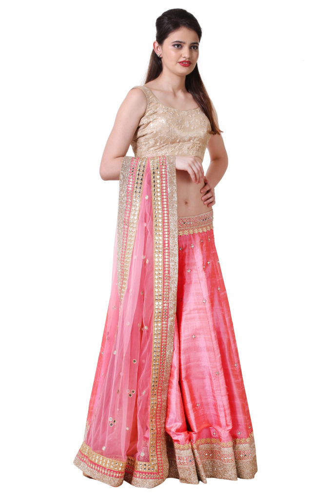 Raw silk lehenga in pink with golden blouse and mirror work dupatta.